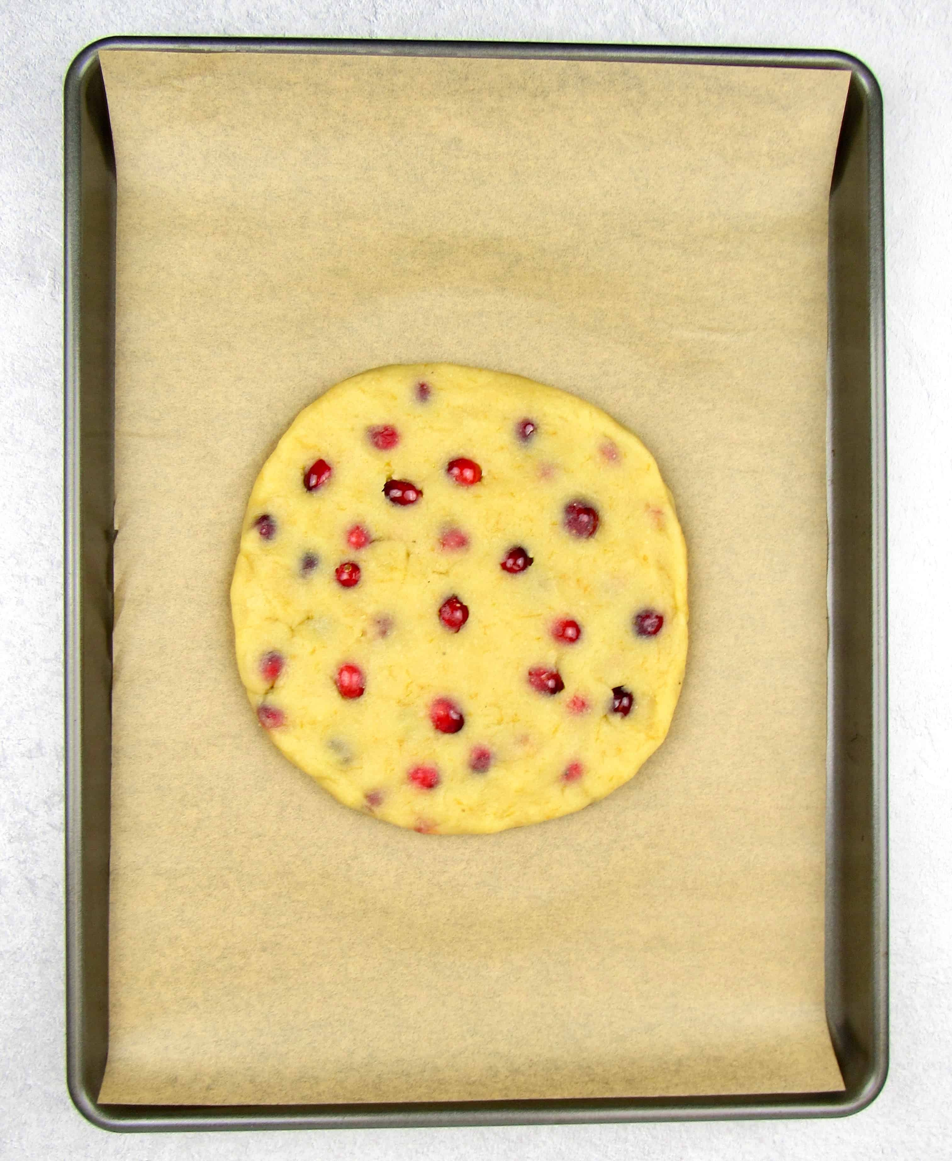 cranberry scones dough in a disc on sheet pan