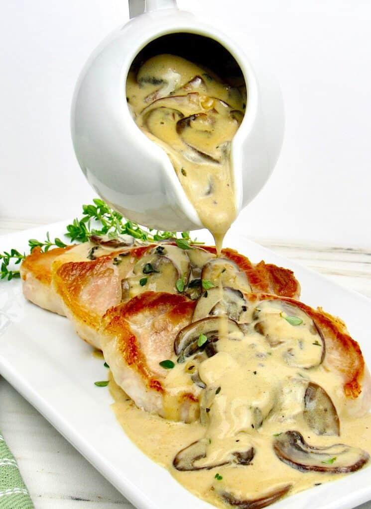 mushroom gravy poured over pork chops on white plate