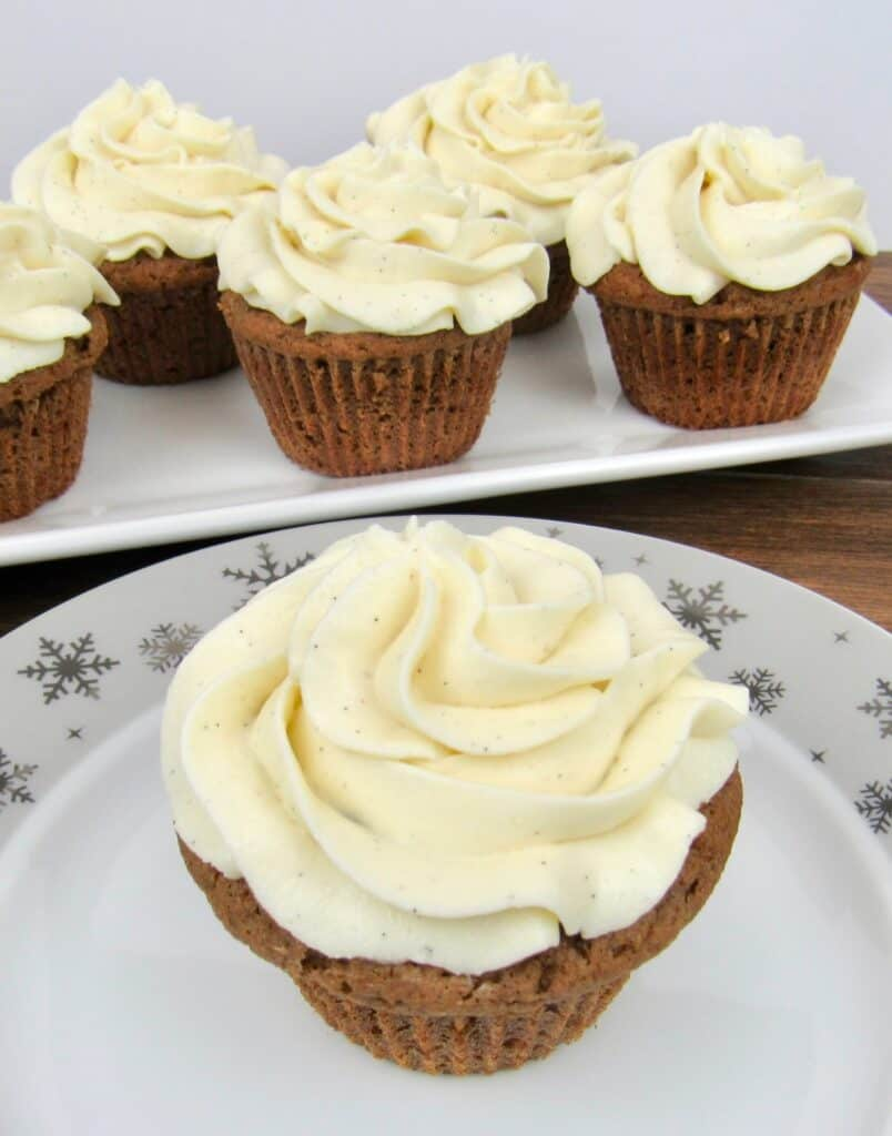 closeup of gingerbread cupcakes on plate with cupcakes on platter in background