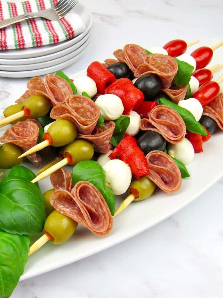 Italian antipasti skewers on white platter plates in background