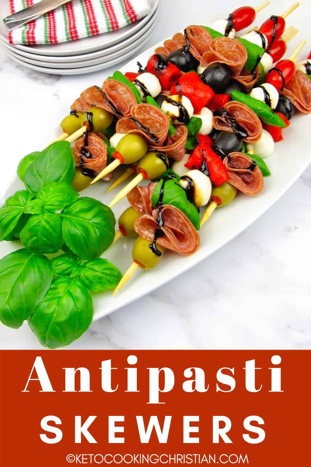 overhead view of antipasti skewers on white platter with basil leaves and balsamic glaze garnish