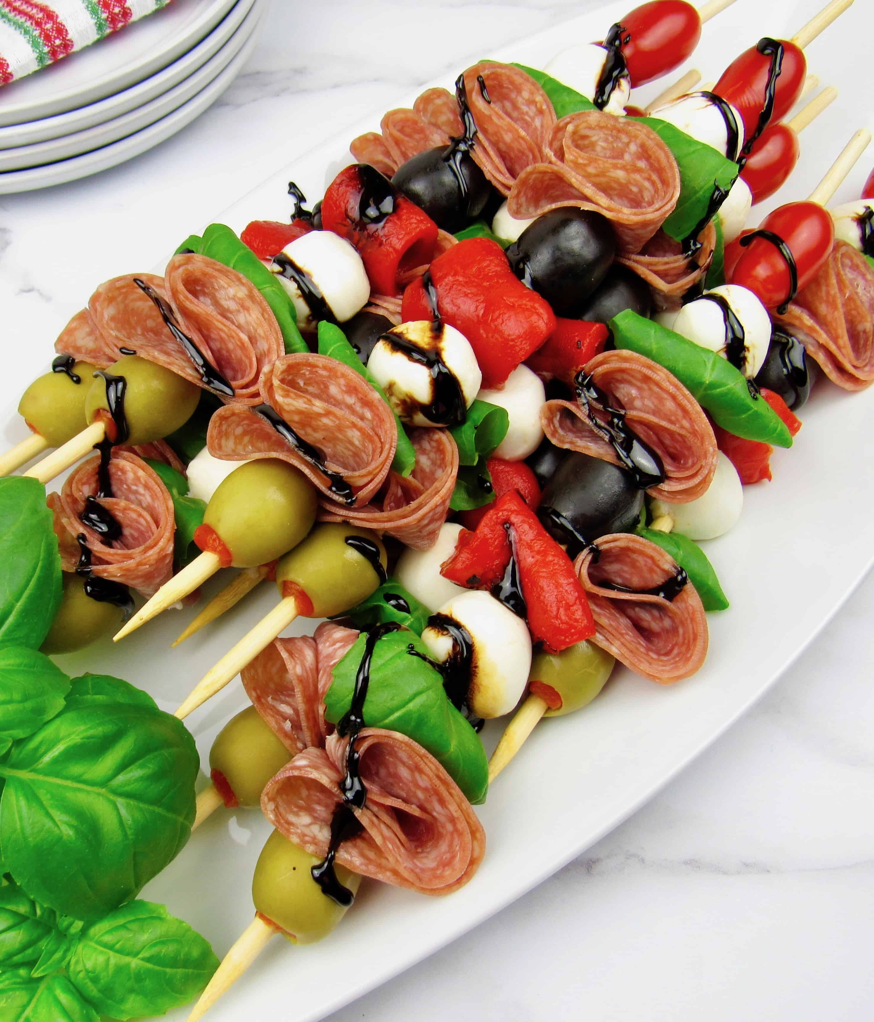 overhead view of Italian antipasti skewers on white platter with balsamic drizzle