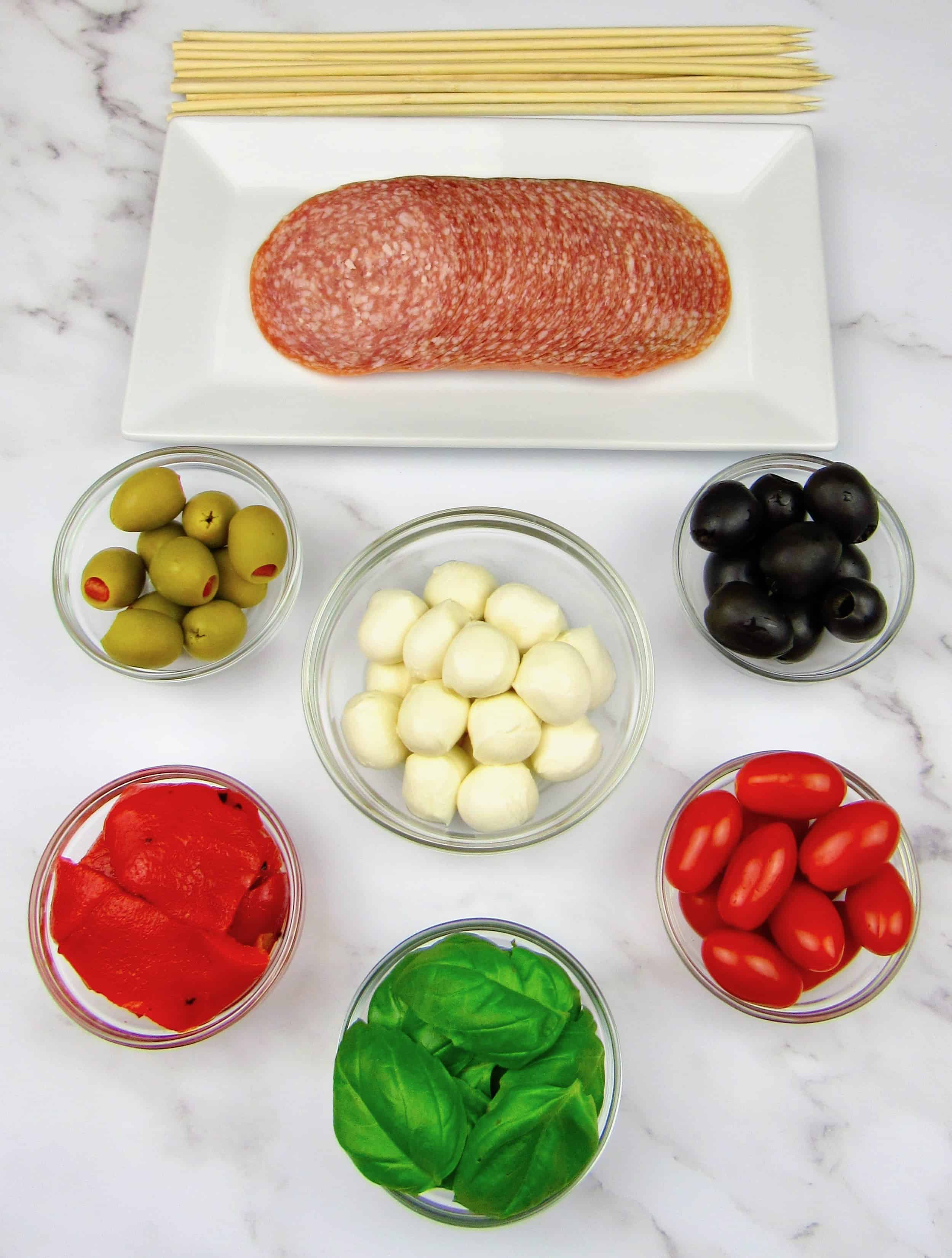 ingredients for antipasti skewers in little glass bowls