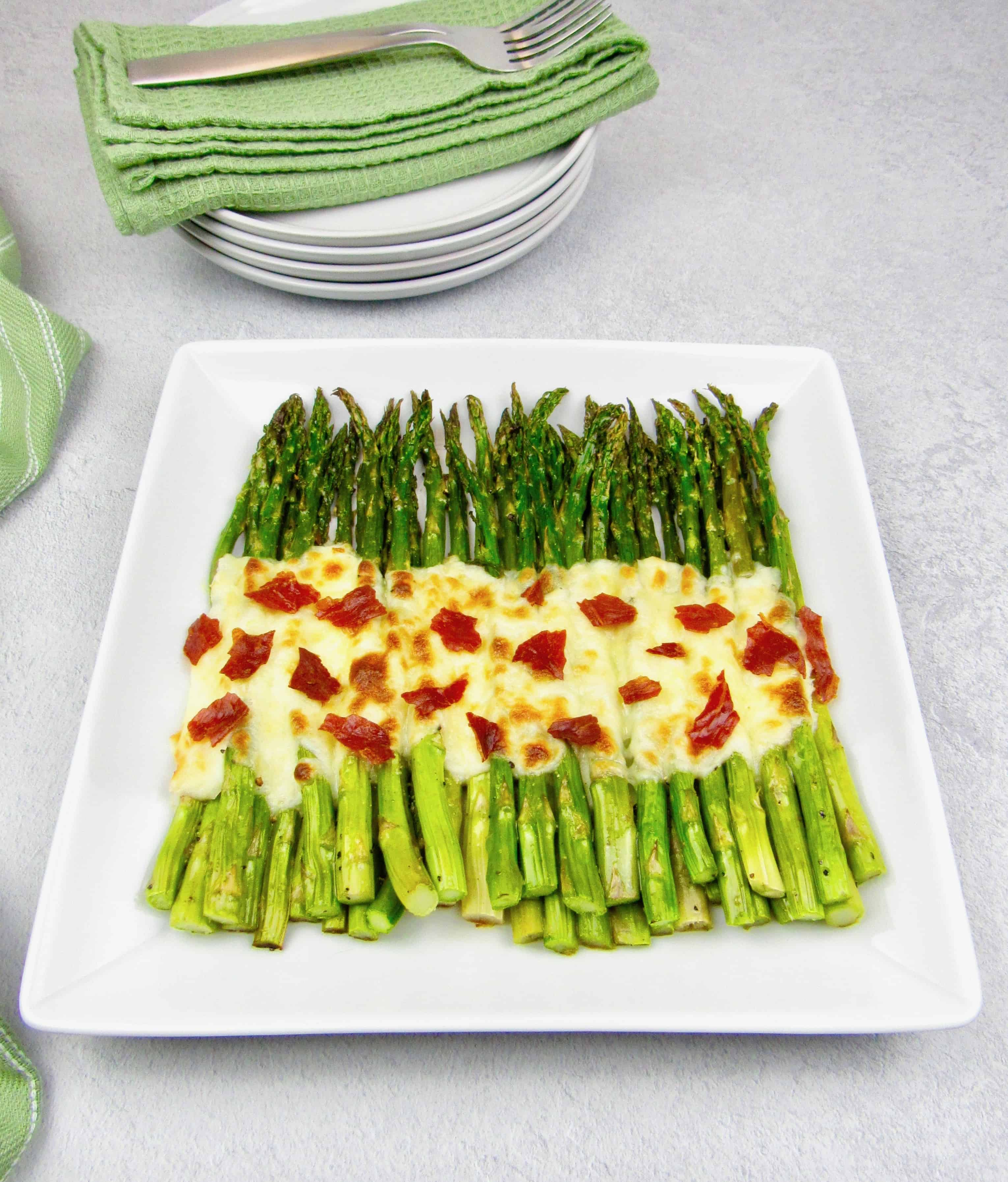 overhead view of roasted asparagus on white plate with melted cheese and crispy prosciutto on top