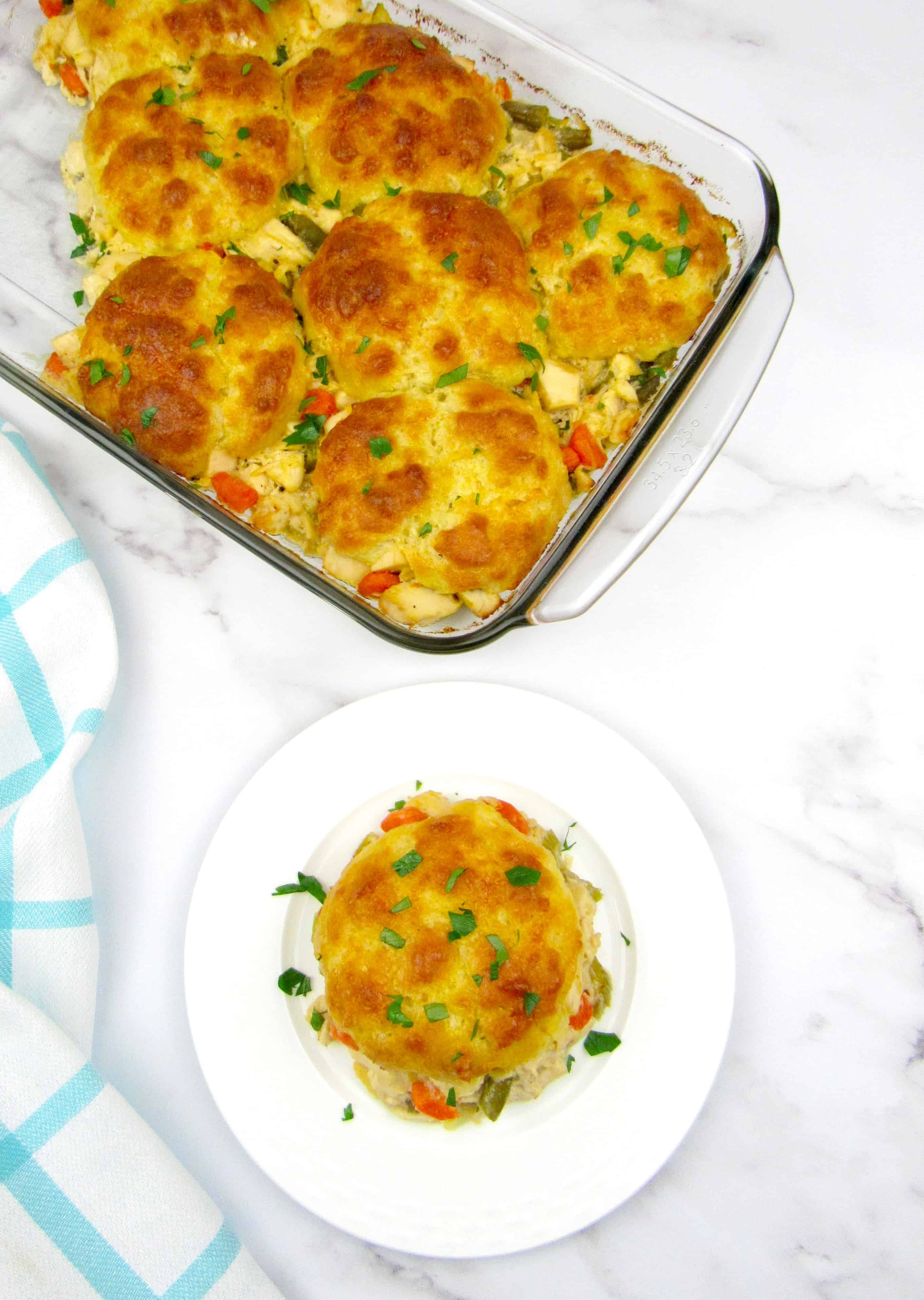 overhead view of piece of chicken pot pie casserole on white plate with casserole in background