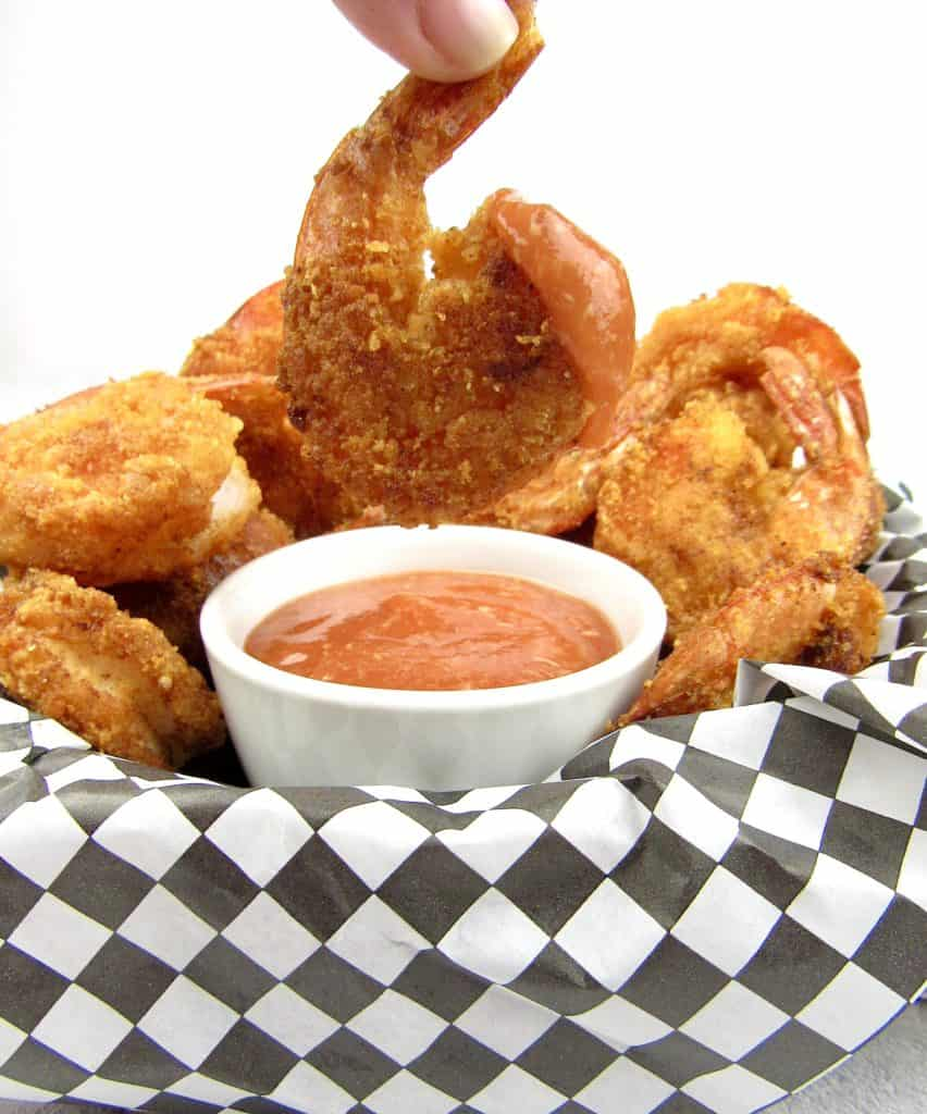 fried shrimp being held up over cocktail sauce