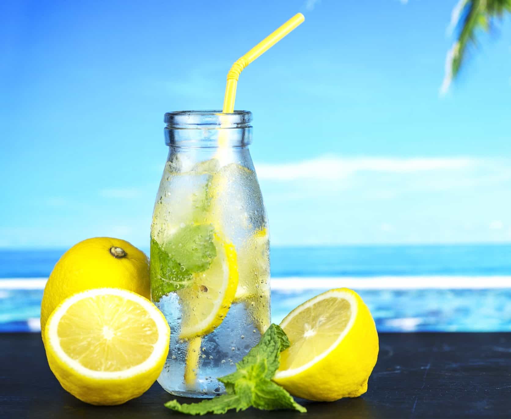 lemons in water with straw ocean in background