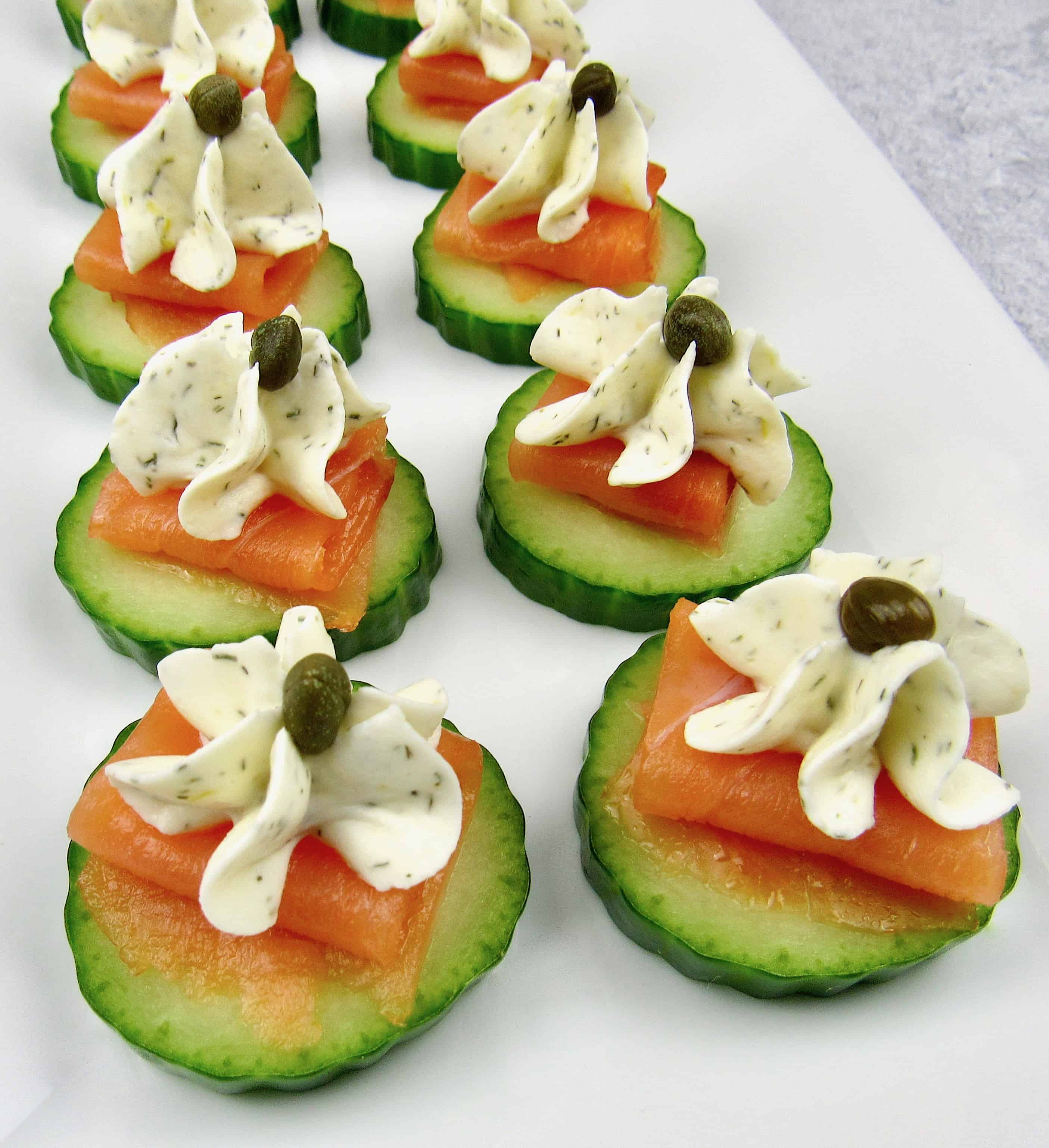 closeup of Smoked Salmon Cucumber Bites with capers on white platter