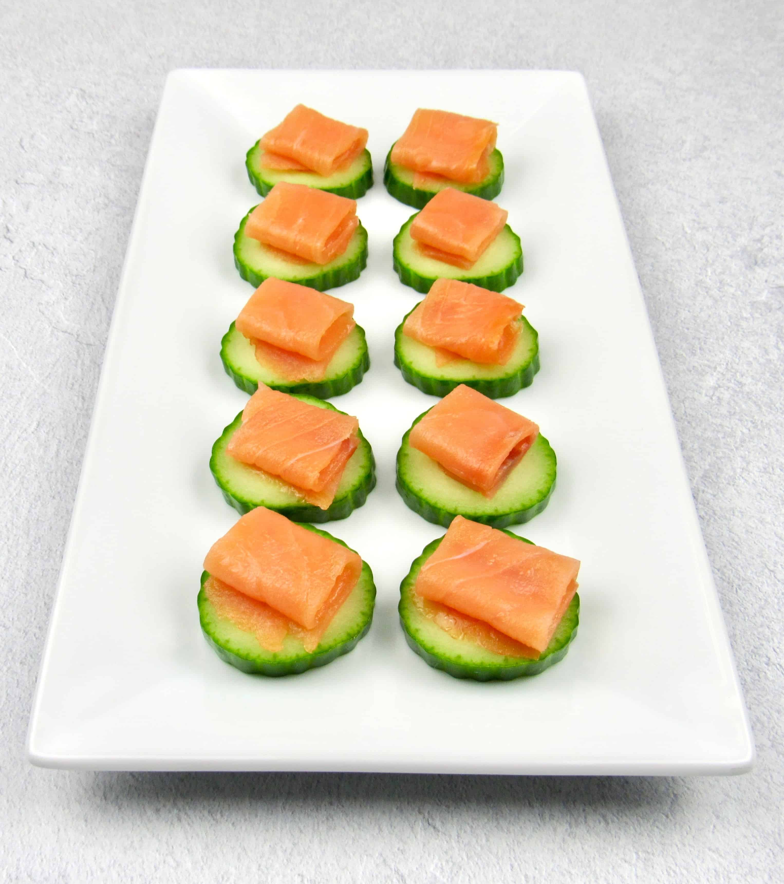overhead view of smoked salmon cucumber bites on white plate