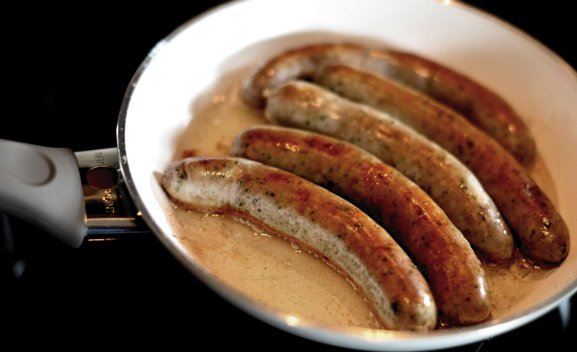 sausage frying in pan