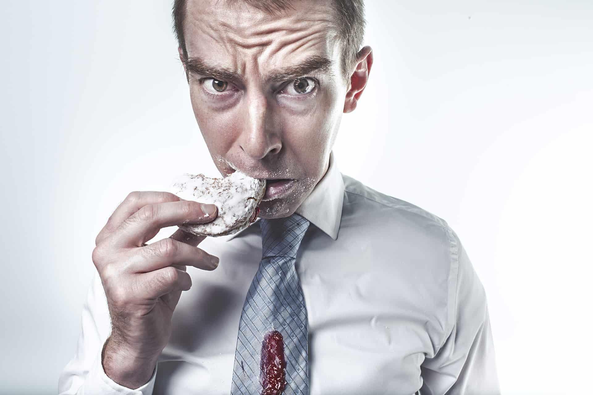 man eating powdered donut