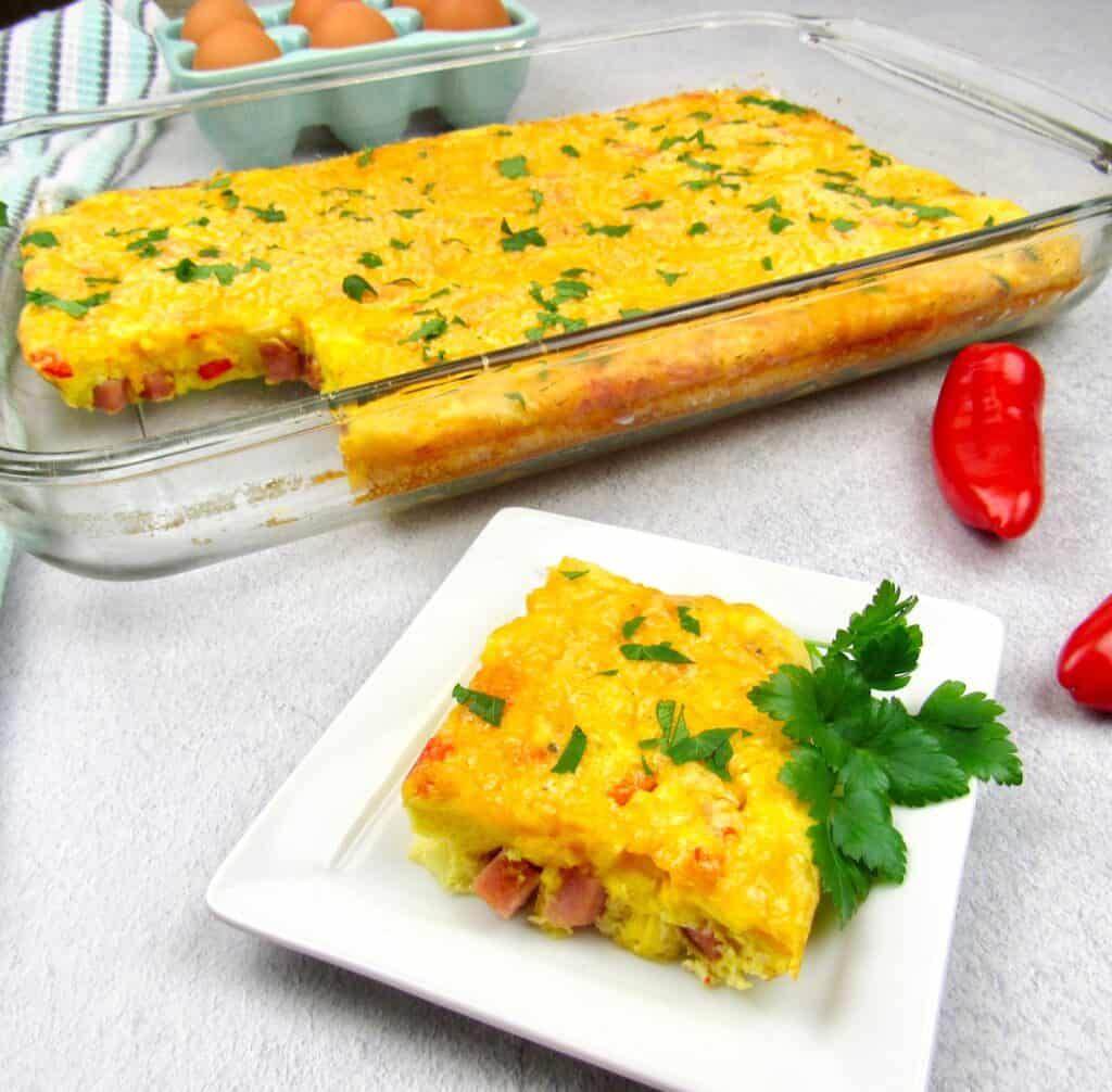 slice of breakfast casserole on white plate with casserole in background