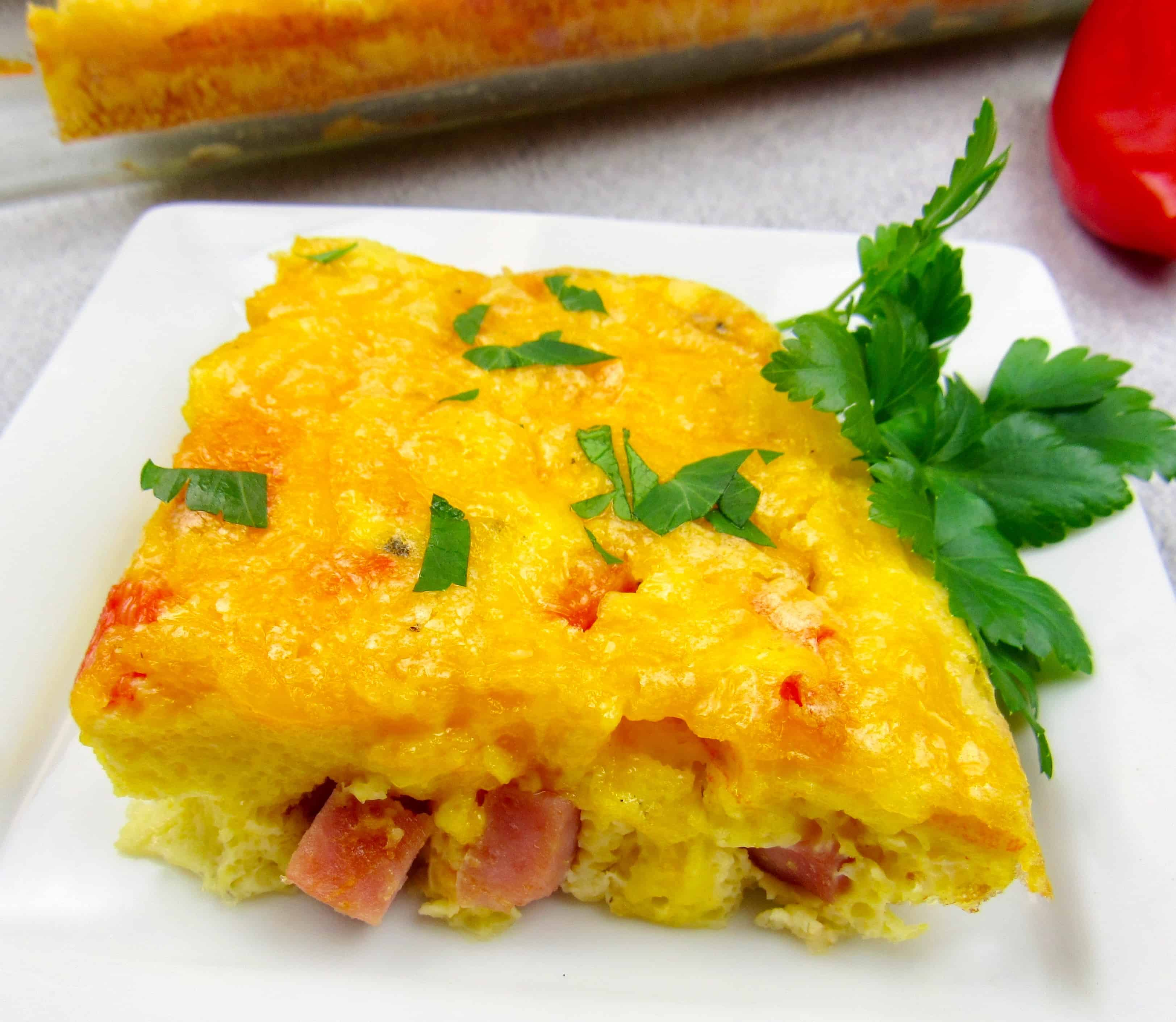closeup of slice of breakfast casserole with ham on white plate