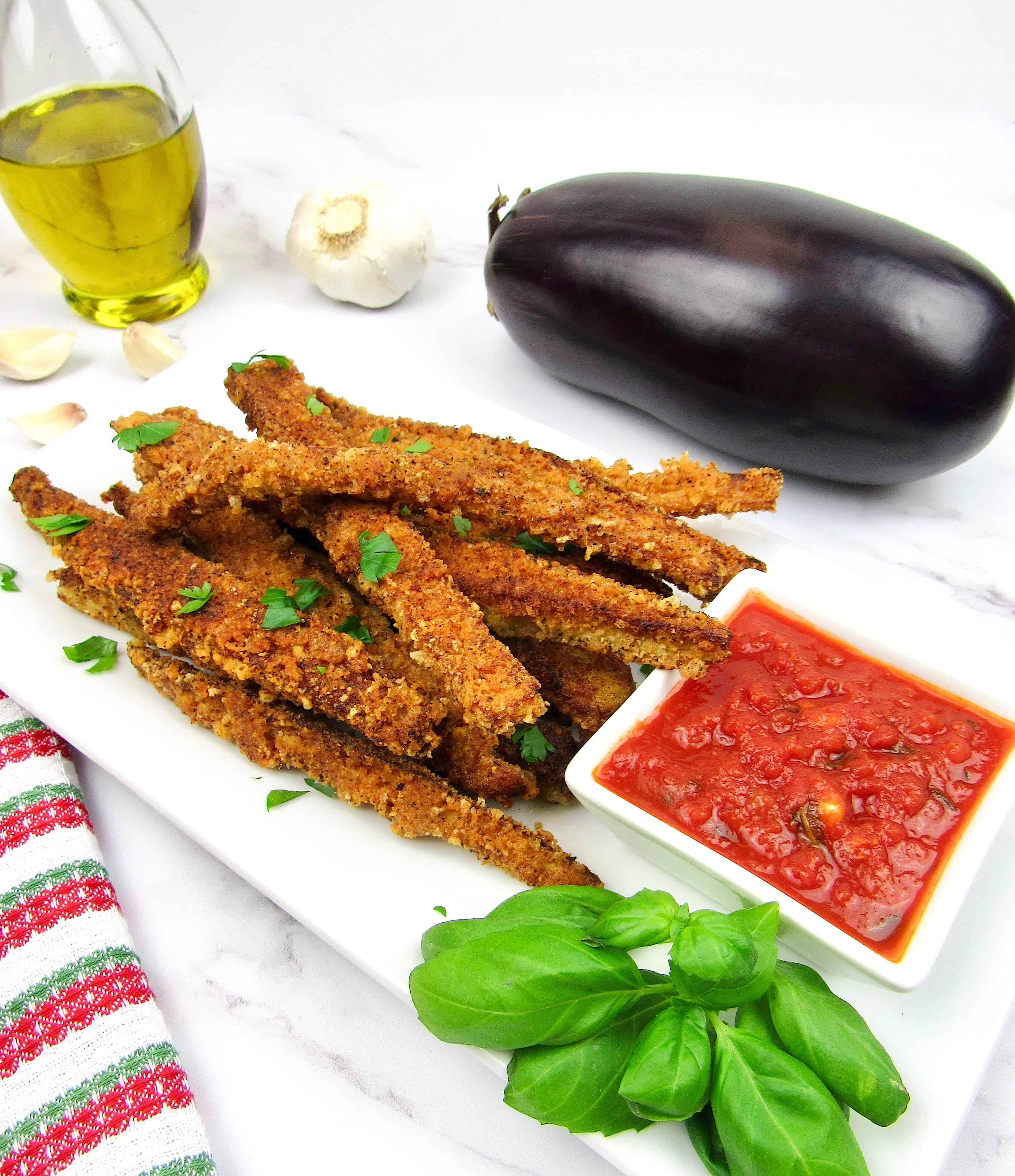 eggplant fries with side of marinara sauce and eggplant in background