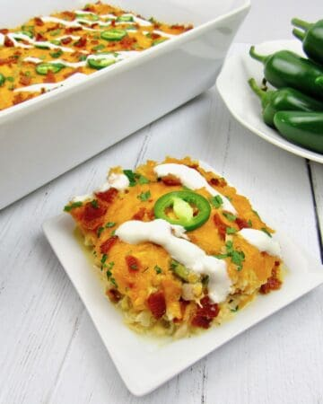 slice of jalapeno popper chicken casserole with casserole and bowl of peppers in background