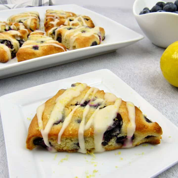 blueberry lemon scone on white plate with more slices in background