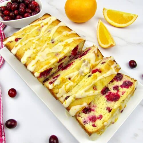 overhead view of cranberry orange bread cut into slices on white plate