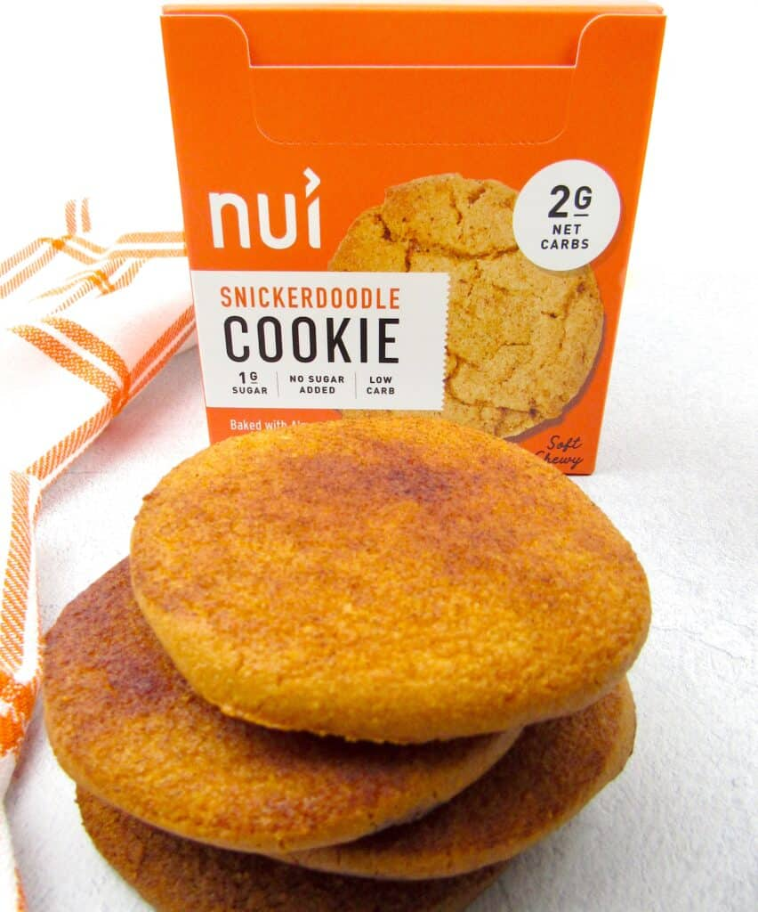 closeup of Nui snickerdoodle cookies in package and stacked in front