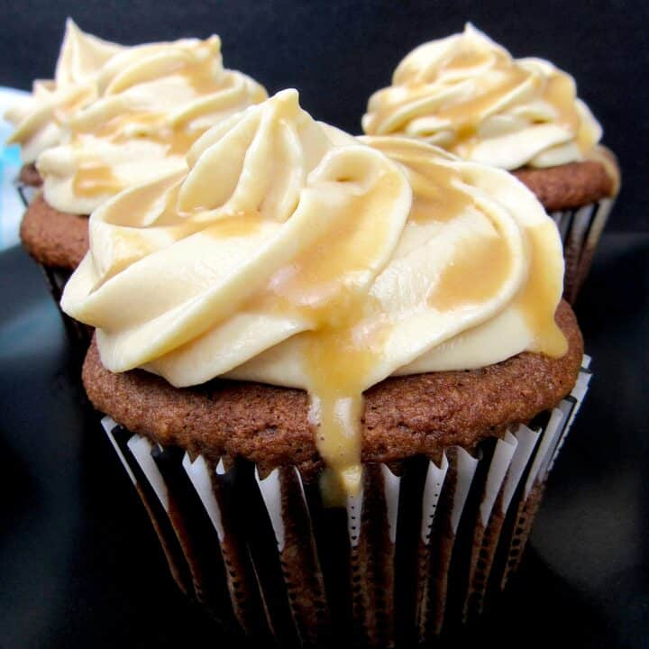 Salted Caramel Chocolate Cupcakes on black plate with caramel dripping off