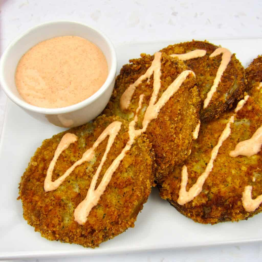 fried green tomatoes with side of dipping sauce on white plate