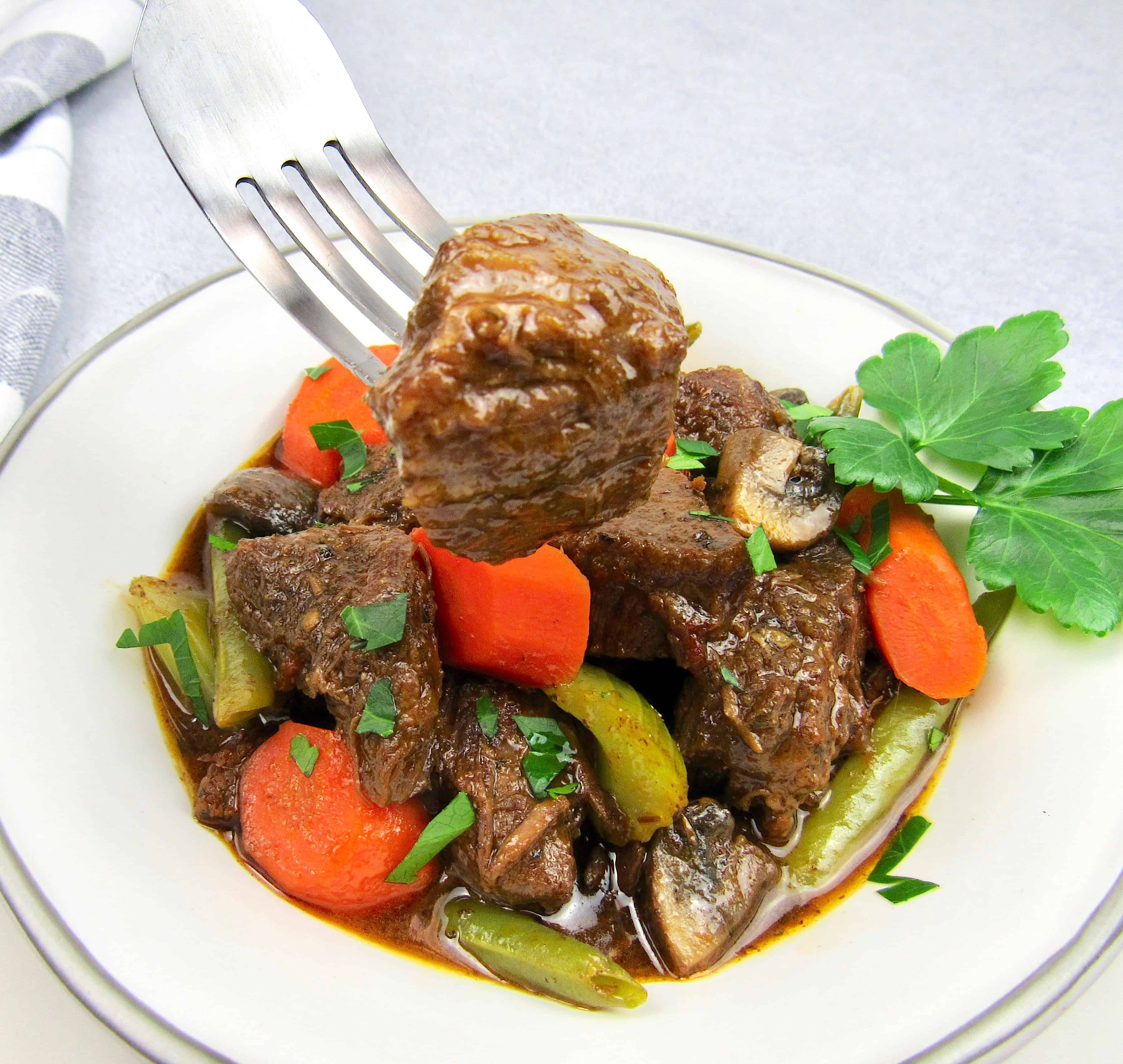 beef stew in white bowl with piece held up with fork