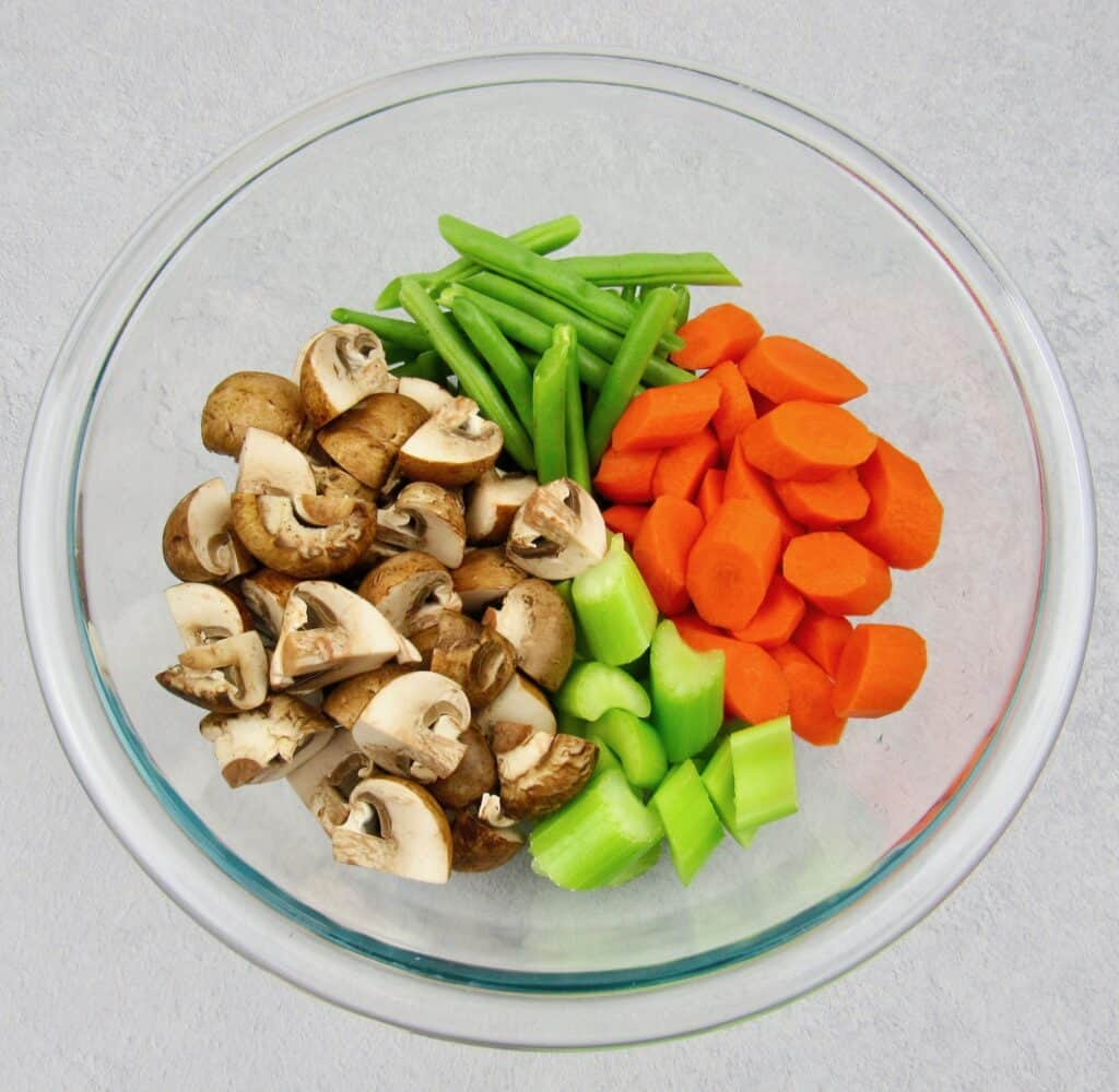 glass bowl with carrots, mushrooms, celery and green beans