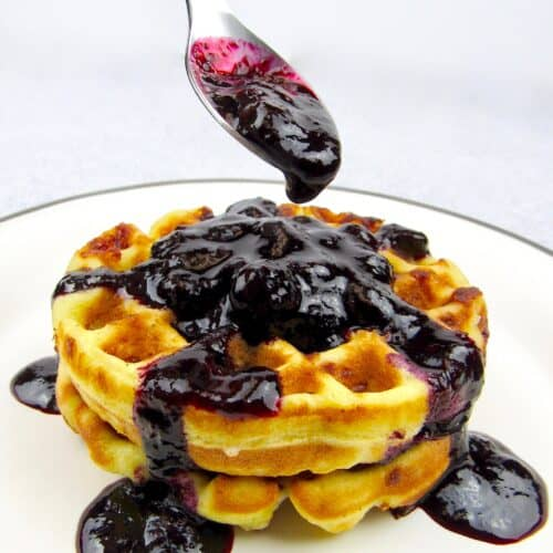 closeup of blueberry sauce in spoon over waffles