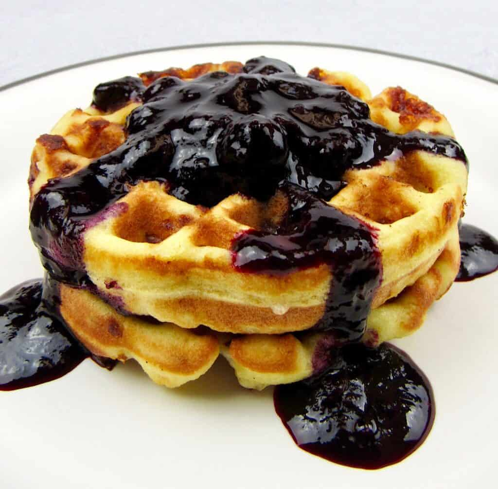 closeup of blueberry sauce over waffles