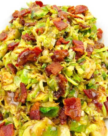 closeup of Brussels Sprouts with Hot Bacon Dressing in white bowl with bacon on top