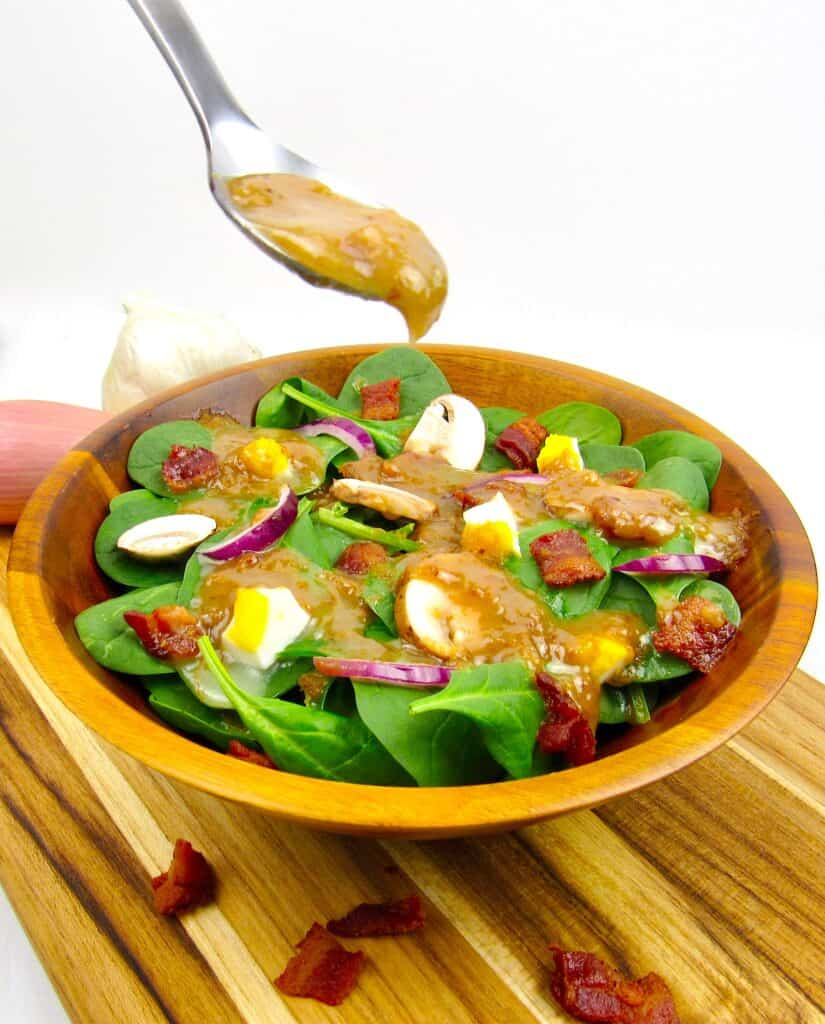 spoonful of hot bacon dressing over spinach salad dripping