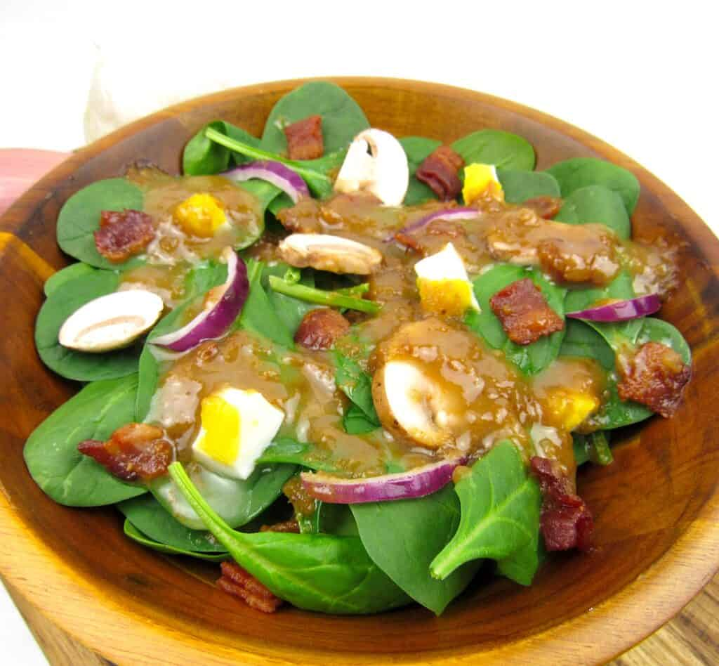 closeup of spinach salad with hot bacon dressing