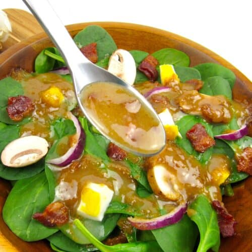 spoonful of hot bacon dressing over spinach salad
