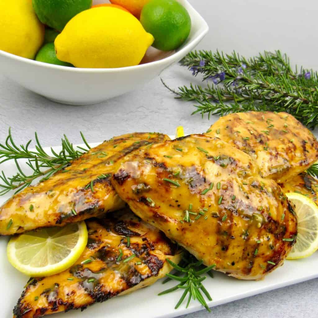 grilled citrus chicken with fruit in background