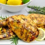 closeup of citrus glazed grilled chicken with bowl of fruit in background