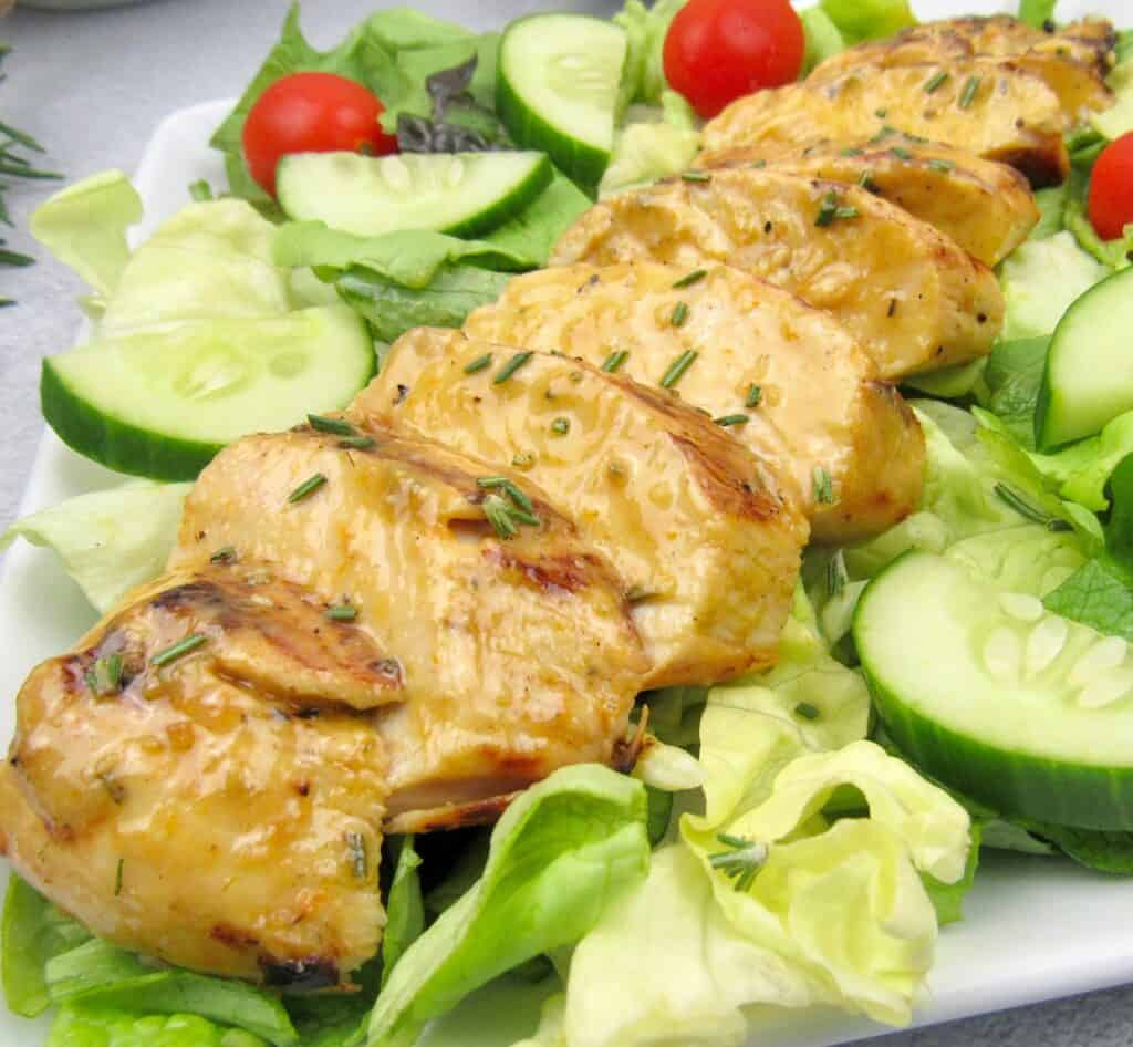 sliced grilled chicken over a salad