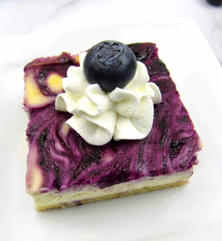 blueberry cheesecake bars with whip cream and a blueberry on top
