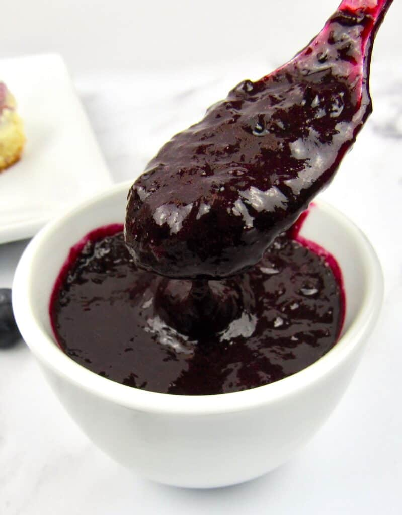 blueberry sauce being spooned out of white bowl