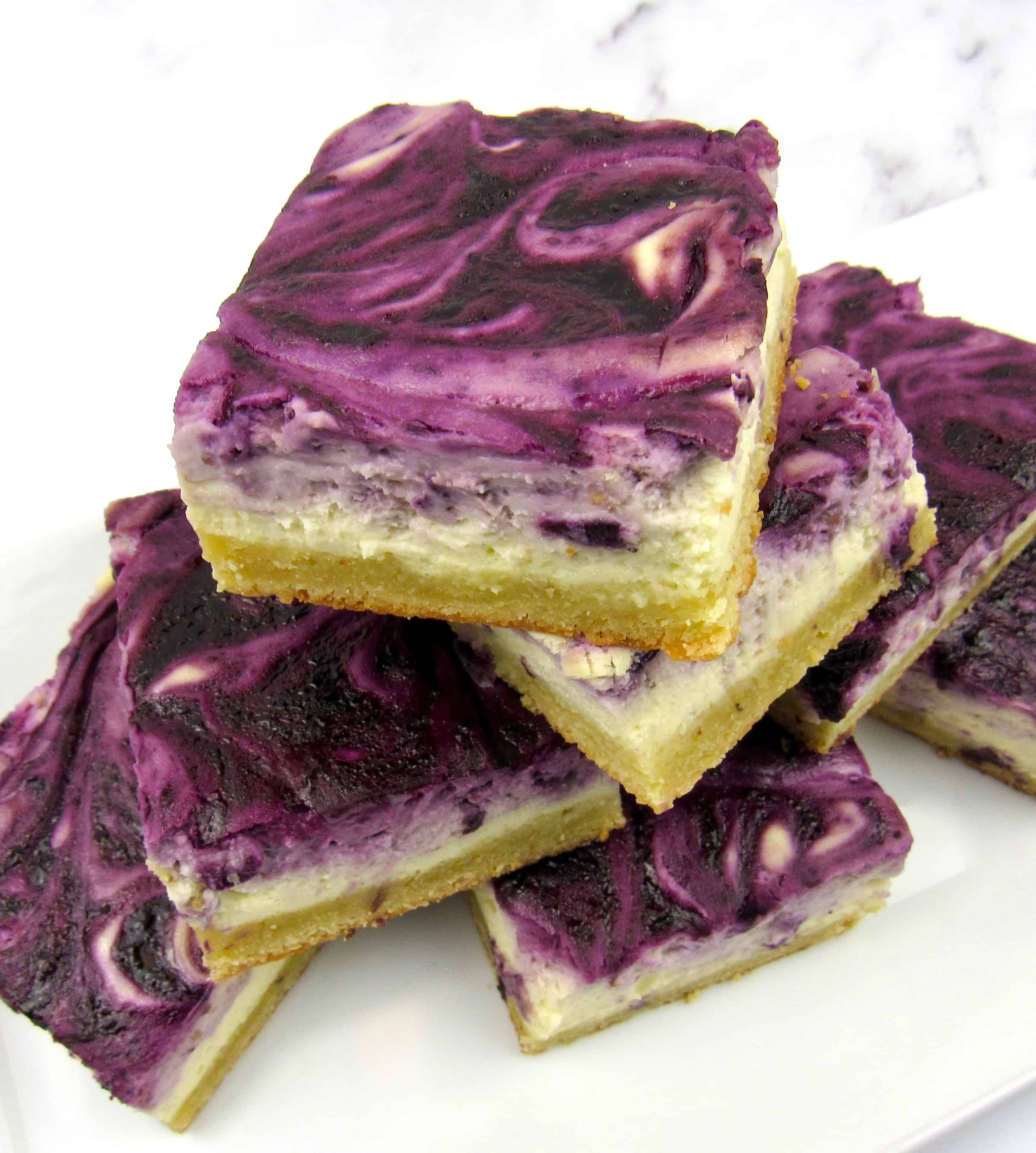 blueberry cheesecake bars stacked up on white plate