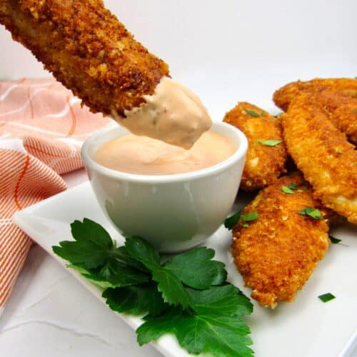 chicken tenders on white plate ong being dipped into dipping sauce