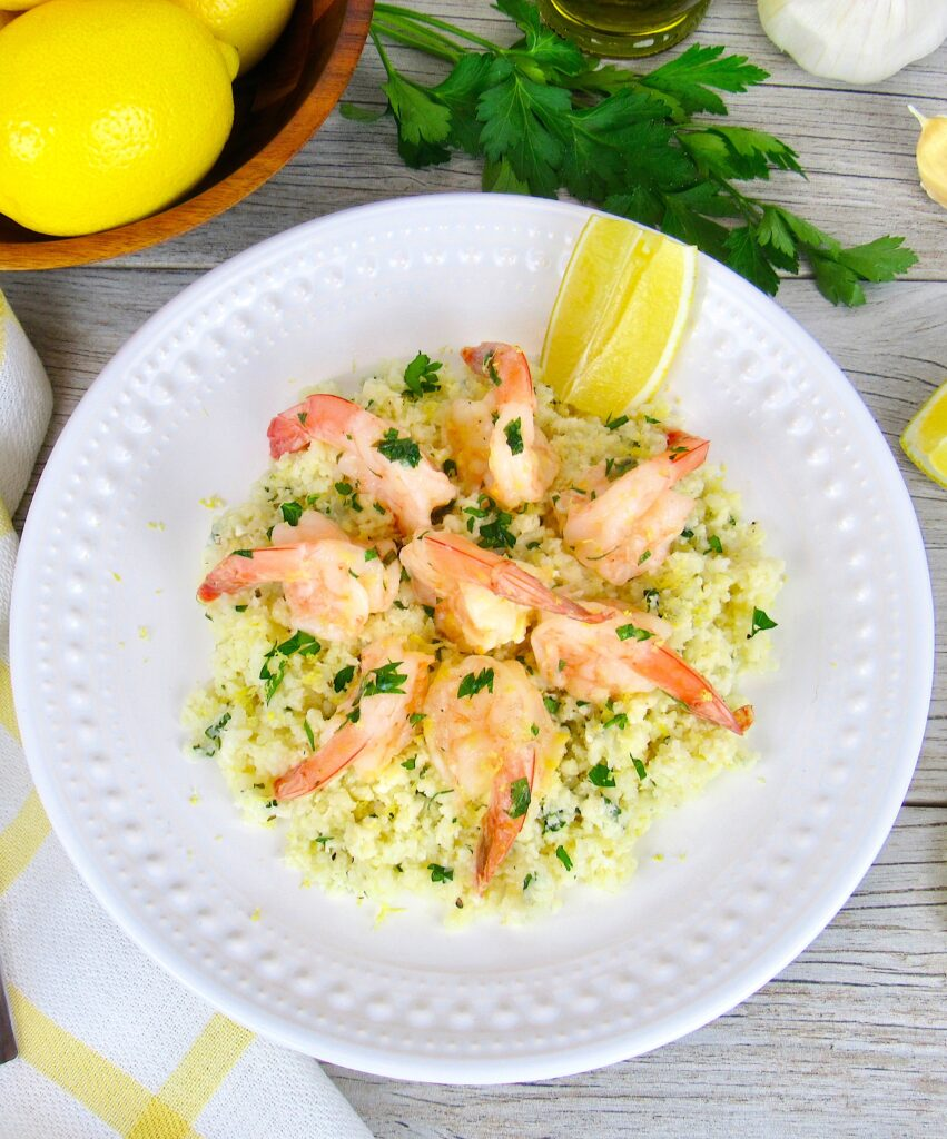 overhead view of shrimp scampi over cauliflower rice on white plate