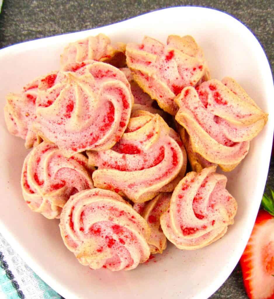 Strawberry Meringue Cookies in white bowl closeup overhead