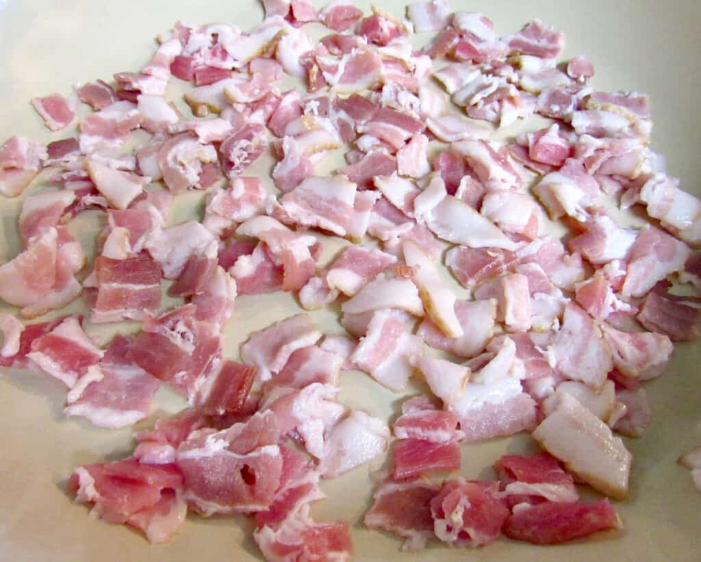 raw bacon pieces in skillet