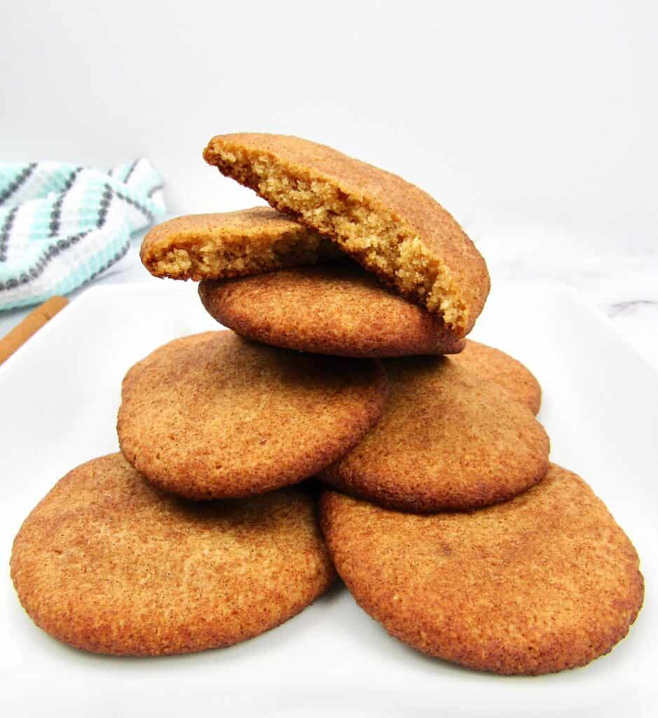 stack of snickerdoodle cookies on plate with one broken in half