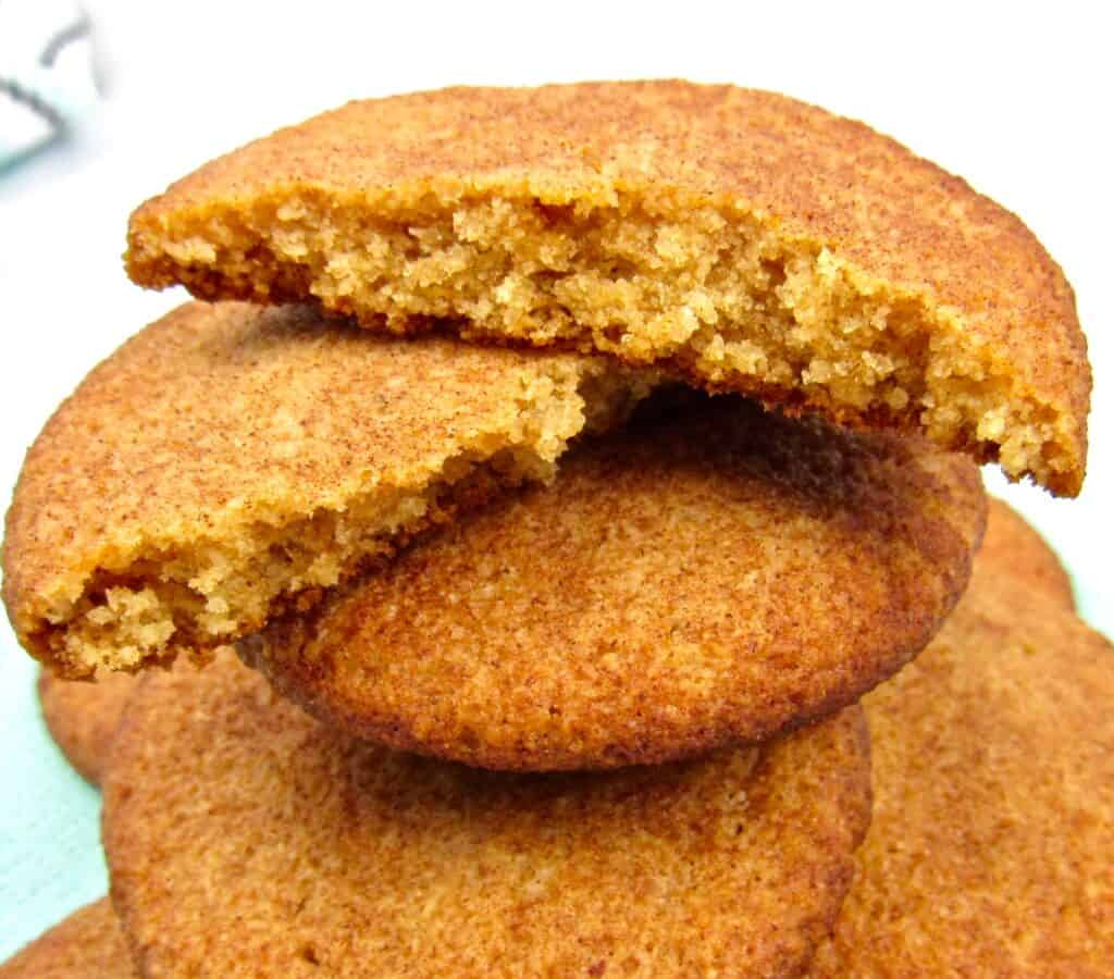 closeup of stack of snickerdoodle cookies on plate with one broken in half