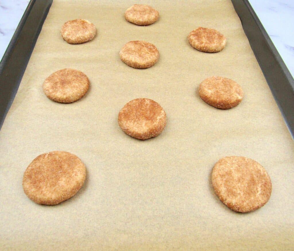 snickerdoodle cookie dough balls on baking sheet flattened