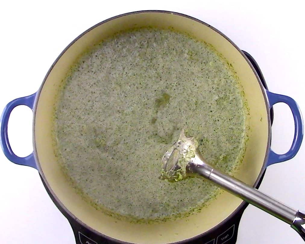 broccoli soup being pureed with immersion blender