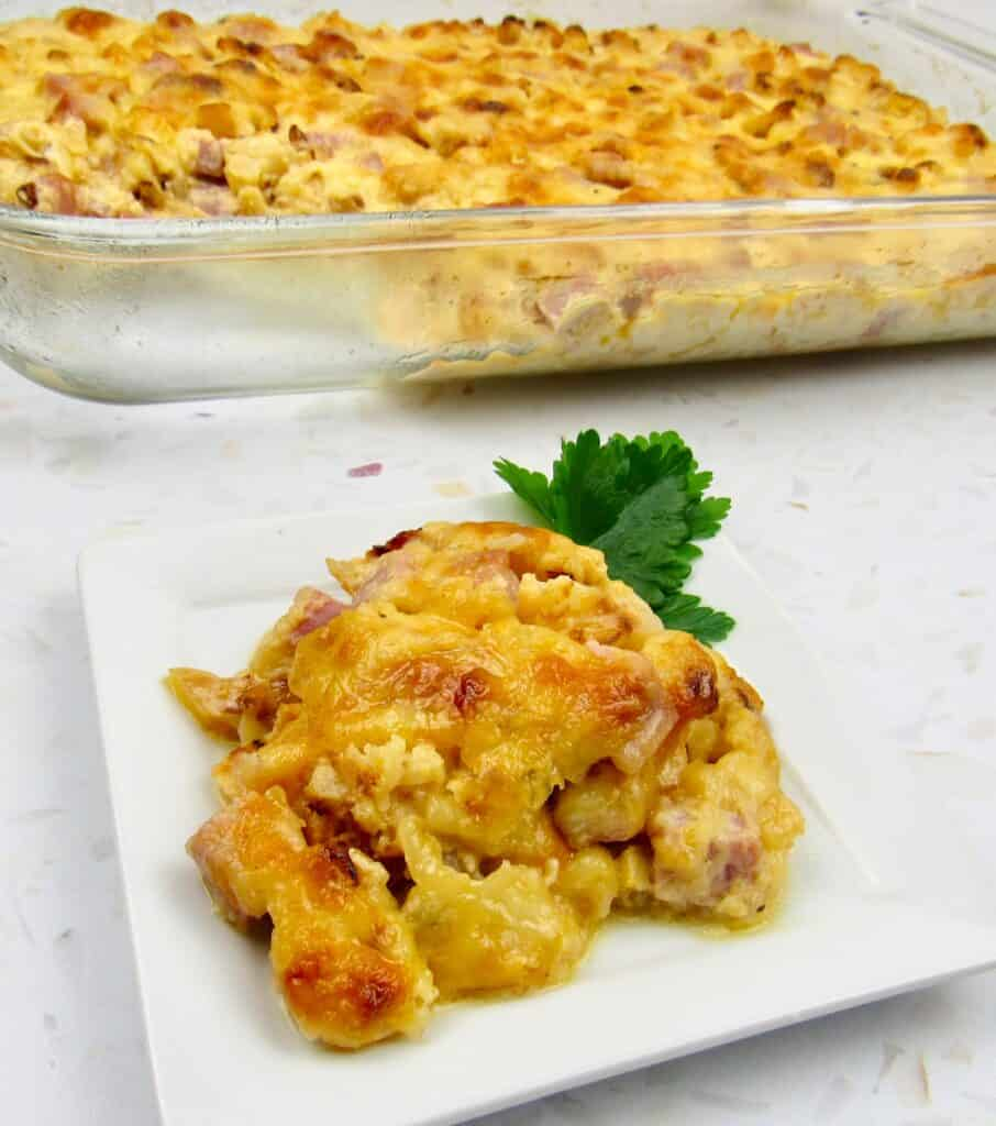 slice of Roasted Cauliflower and Ham Casserole on plate with casserole in background