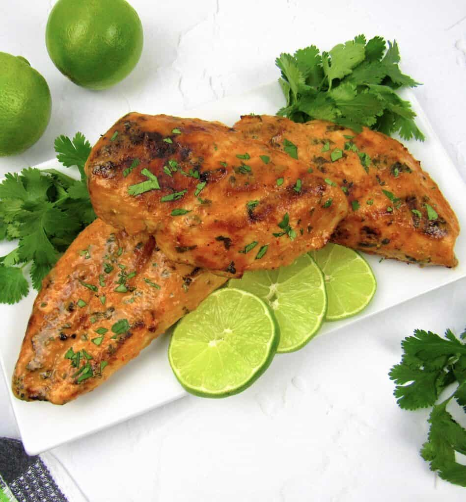 thai red curry grilled chicken on plate with limes and cilantro
