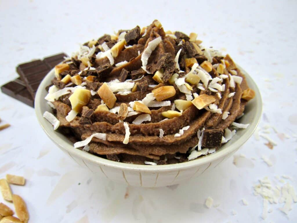 bowl of chocolate mousse with coconut and almonds on top