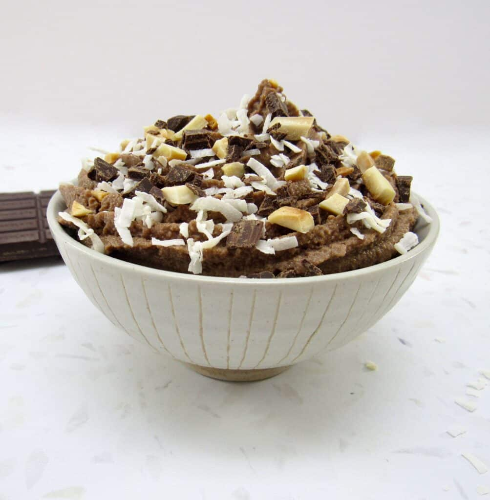 bowl of chocolate mousse with coconut and almonds